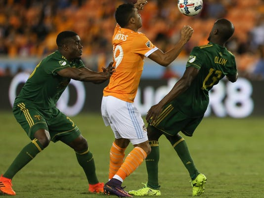 Houston Dynamo forward Mauro Manotas (19) battles with Portland Timbers players Larrys Mabiala (33) and Lawrence Olum (13) for possession of the ball during the MLS Western Conference semifinal soccer match Monday, Oct. 30, 2017, in Houston. (Yi-Chin Lee/Houston Chronicle via AP)