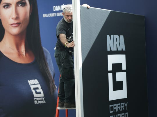 Dave Ross with Local 770, works on setting up a virtual reality stall where participants at the NRA's Carry Guard Expo can run through self-defense scenarios. A poster of Dana Loesch, an NRA spokeswoman and talk radio host, is in the background.