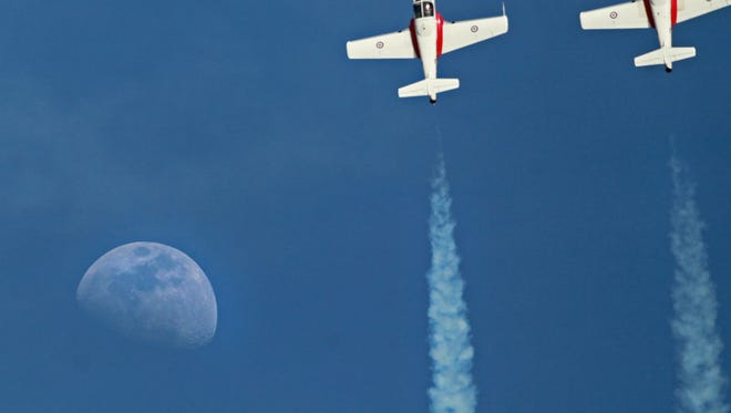 The Royal Canadian Snowbirds team fly by the moon during the Anderson Regional Airshow.