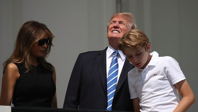 President Trump looks up toward the Solar Eclipse while standing with his wife first lady Melania Trump and their son Barron, on the Truman Balcony at the White House on August 21, 2017 in Washington, D.C.