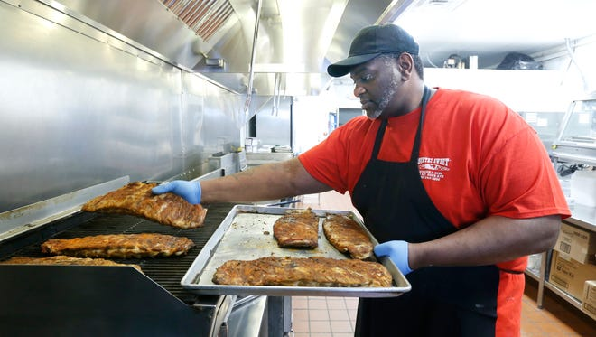 Assistant manager Patrick Schuyler places ribs on the grill at Country Sweet Chicken & Ribs, which is reopening after damages from a fire at the Mt. Hope location.