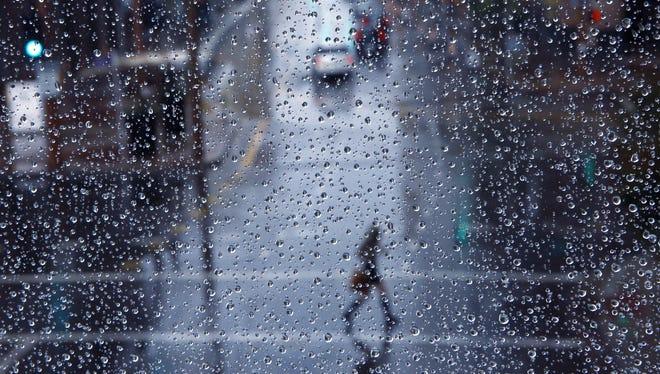 A pedestrian navigates through the rain along Central Avenue in Phoenix on Feb. 18, 2017.