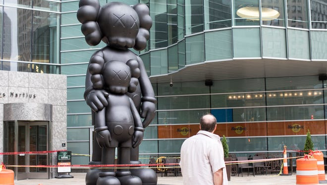 """A pedestrian passes by the 17-foot statue titled """"Waiting"""" by  artist Kaws at the main entrance to One Campus Martius in Detroit, Sunday, May 20, 2018."""