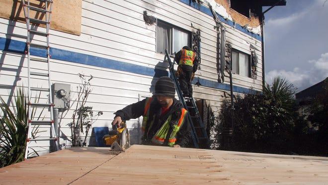 Daniel Guzman of 1-800-BoardUp cuts a window cover Thursday outside the fire-damaged Blue Water Inn in Kingston.