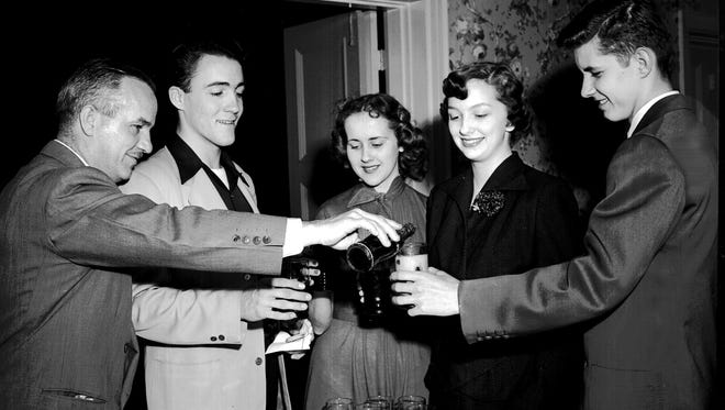 """January 16, 1951 - ESSAY CONTEST PLANNED - The Advertising Club of Memphis held a party for high school editors on Jan. 16, 1951, at which the club's second annual high school essay contest was explained to the young journalists. The essays will be on """"What Advertising Means to Me.""""  Winners will receive Savings Bonds and a chance to compete for a $500 national prize. With all the rules understood, P.N. Baldwin (left) of the Advertising Club poured soft drinks for (from left) Bill Bagwell of 1874 York, a Catholic High student; Jane Simpson of 1881 Wellington, Sacred Heart student; Ann Knox of 872 Sheridan, Central student; and Jimmy Eikner of 298 Waverly, a student at Messick."""