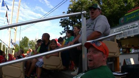 Larry Smith, top, and Patrick Bertrand cheer loudly for the Green Bay Bullfrogs game earlier this month. The two became friends after sitting next to one another for every game.