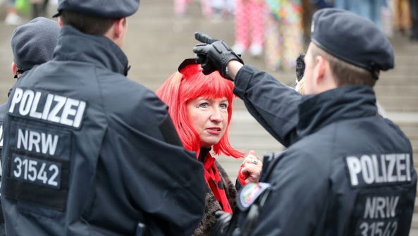Members of the German police talk to a woman wearing