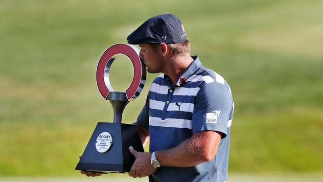 Bryson DeChambeau kisses the Rocket Mortgage Classic trophy Sunday at Detroit Golf Club in Detroit. DeChambeau won the tournament by three strokes for his first victory of the season and sixth overall.