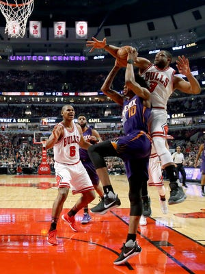 Chicago Bulls' Dwyane Wade, right, tries to block the shot of Phoenix Suns' Derrick Jones Jr. (10) during the first half of an NBA basketball game Friday, Feb. 24, 2017, in Chicago.