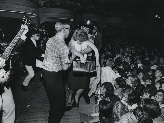 The crush was so bad and the room so hot and stuffy at the Dave Clark Five show that some in the audience passed out.  One girl was carried across the stage, past the performers, to the wings, where a makeshift infirmary was set up. This photo was published in the June 8, 1964, Milwaukee Journal.