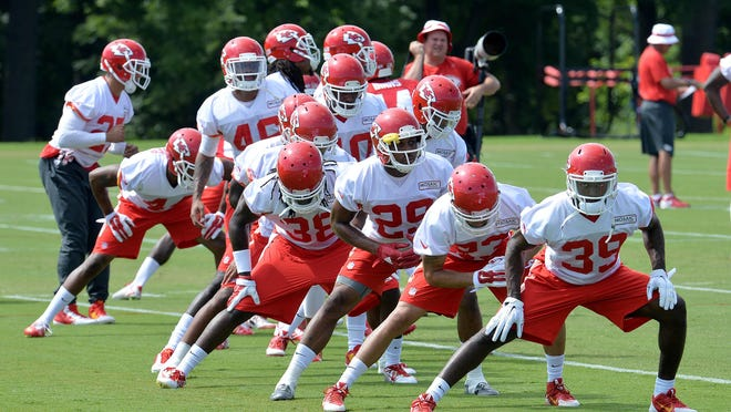 Kansas City Chiefs defensive players stretch during the first full-squad workout of training camp on Saturday in St. Joseph.