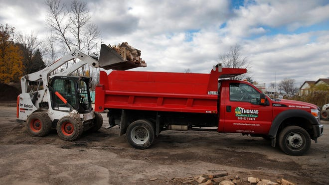 Frank Heinlein, a worker at Thomas Landscape and Garden Center in Webster loads a truck with fire wood for delivery.  There is a shortage of wood this year due in part to last years' very cold winter. Thomas offers delivery of wood through the first week of December.