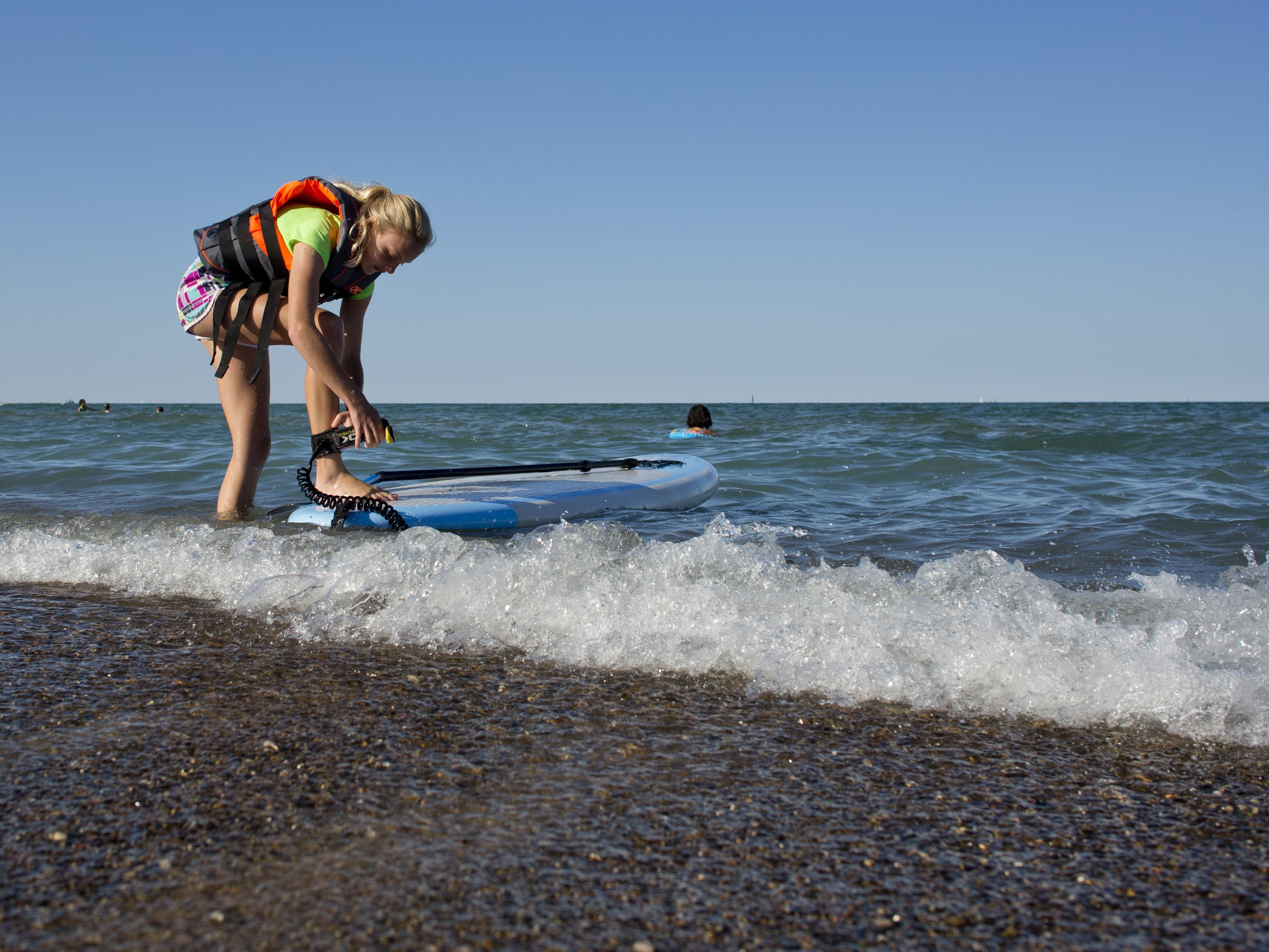 Grace Stein, 13, of Port Huron, secures the board to her leg during a stand up paddle board class Wednesday, July 22, 2015 at Lakeside Beach in Port Huron.