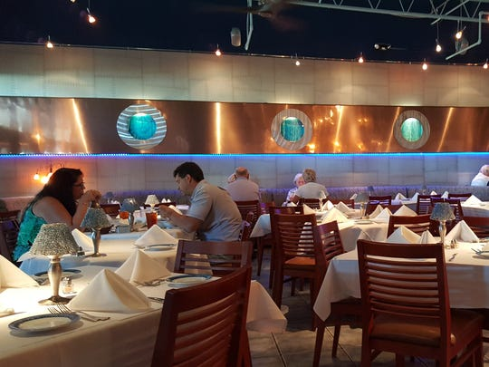 The dining room at USS Nemo in Naples is warm and inviting, with a cute nautical theme that includes portholes.