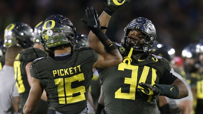 Oregon's Nick Pickett (16) and Jordon Scott celebrate a fourth-quarter stop by the Duck defense against Wisconsin in the Rose Bowl. [Chris Pietsch/The Register-Guard] - registerguard.com
