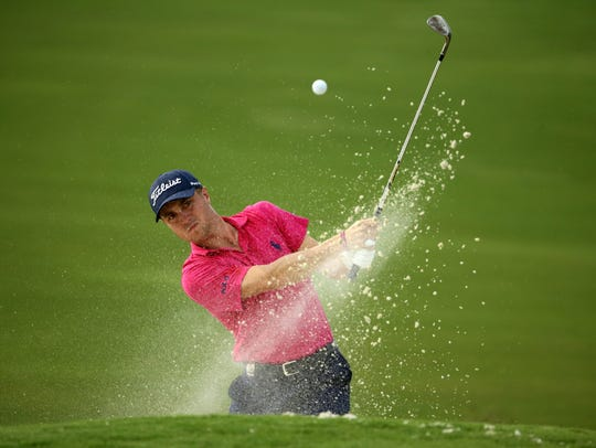 Justin Thomas plays from a bunker on the 16th hole