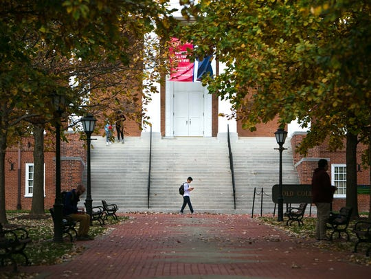 Students hang around Old College near Main Street on the UD campus, where enrollment is up again this year.