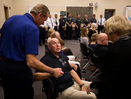 Retired police officer Bill Handworth, left, greets