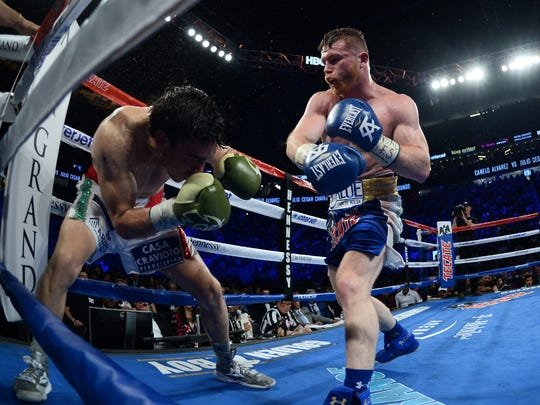 Canelo Alvarez, right, connects with a right hand as Julio Cesar Chavez Jr. cowers in the corner.