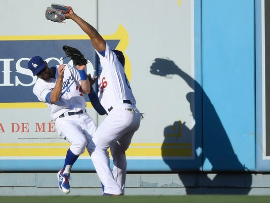 Los Angeles Dodgers right fielder Yasiel Puig, right, catches a fly ball hit by Chicago Cubs' Kris Bryant over the top of center fielder Chris Taylor during the first inning of Game 2 of baseball's National League Championship Series in Los Angeles, Sunday, Oct. 15, 2017. (AP Photo/Mark J. Terrill)