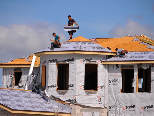 Roofers install a roof on a new home under construction