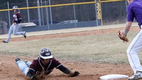An Owen player slides into third base during a game against North Henderson.