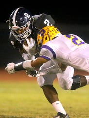 Smyrna's Percy Whittaker (2) makes a tackle during