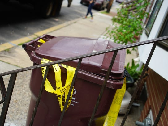 Crime tape hangs from a garbage can on Pine Street