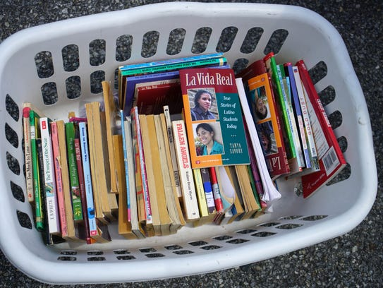 Free books sit in a laundry basket in the parking lot