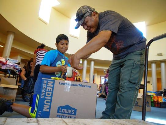 Gabriel Guzman, 10, and Angel Martinez, volunteer their