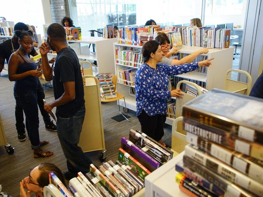 Volunteers sort and put books on shelves at the Route