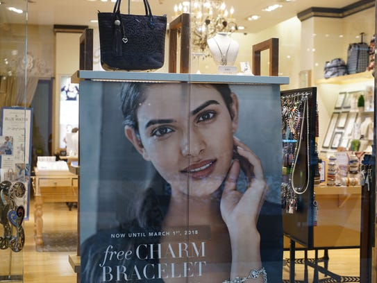Advertisements are displayed in a store window at Christiana Mall, where shoppers still flock to despite the growing trend of e-commerce disrupting the retail industry.