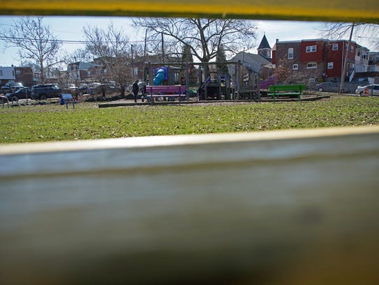 Children play on old equipment in Father Tucker Park