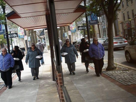 Patrons of a nearby restaurant walk along Loockerman