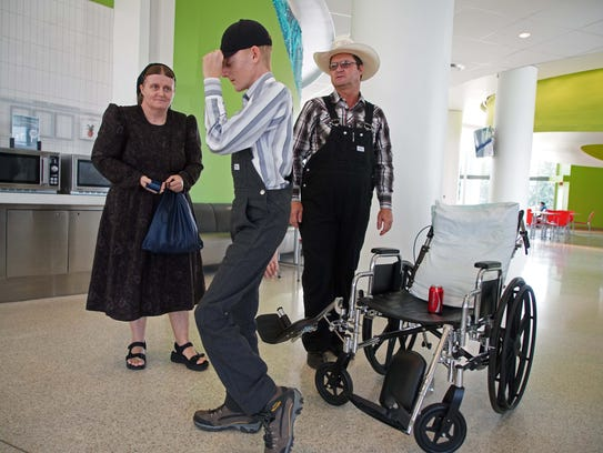 Gerhard Friessen Fehr, a 15 year-old teenager from a Mennonite colony near the Yucata‡n Peninsula stands up from his wheel chair while recovering from spine surgery at Nemours/A.I. duPont Hospital for Children Hospital. Parents Helena and Gerhard watch on in the hospital cafeteria.
