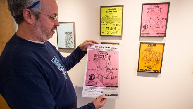Kevin Shapiro, the archivist for Phish, shows the poster for a new exhibit of posters and artwork from the band's career at the Amy E. Tarrant Gallery in Burlington on Monday, October 2, 2017. The poster shows a leaflet from one of the band's earliest shows at the University of Vermont's Slade Hall.