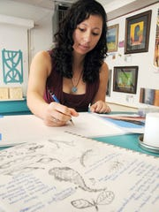 Kami Koyamatsu works on her artwork on Monday at Desert Roots Gallery. Koyamatsu's sketches are pictured in the foreground.