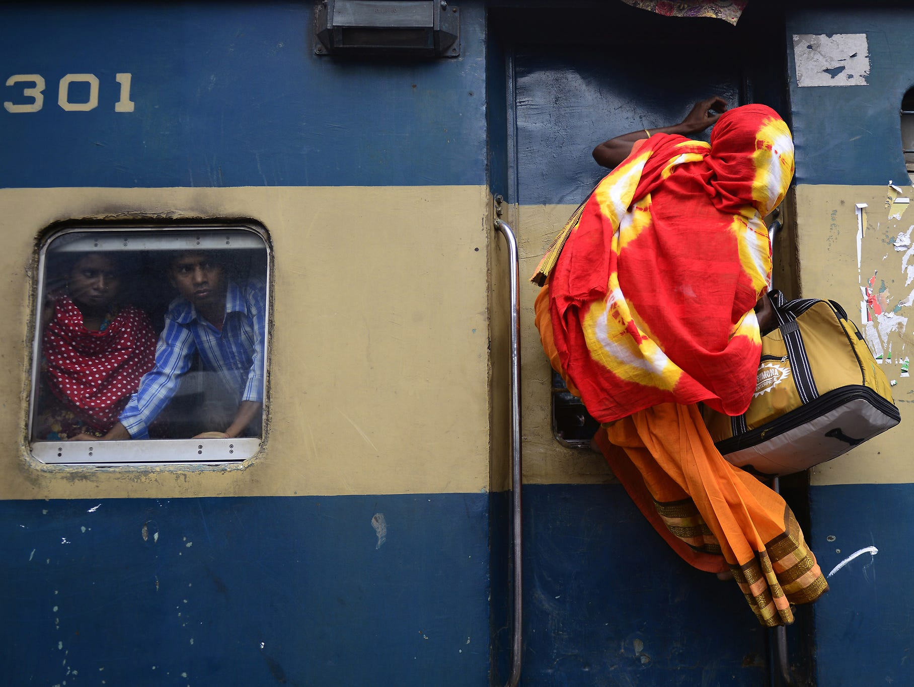A woman climbs onto a train as people rush home to their villages to be with their families before the start of Eid al-Fitr festivities in Dhaka, Bangladesh.