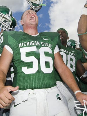 MSU football players including Jehuu Caulcrick (30), Alex Shackleton (56) and Dwayne Holmes (right) sing the fight song by the student section after defeating Pittsburgh Saturday, September 15, 2007, in East Lansing.