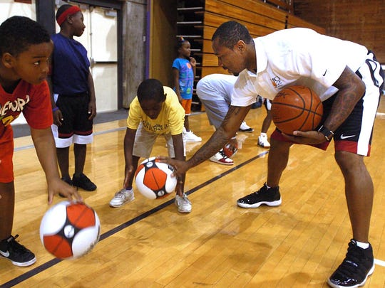In this file photo, Mo Williams, right, instructs Will Owens, 10 (left) and DeAndre Collins, 8, on proper ball handling technique during his basketball camp at Millsaps College in Jackson.