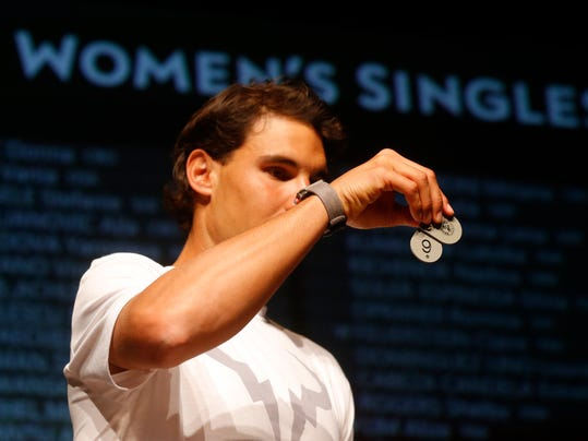 Defending champion Spain's Rafael Nadal holds a token during the Women's singles draw for the French Open Tennis tournament, at the Roland Garros stadium in Paris, Friday, May 23, 2014. The French Open tennis tournament starts Sunday. (AP Photo/Michel Euler)