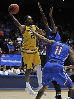 Michigan's Zak Irvin passes under pressure from Tulsa in the first half.