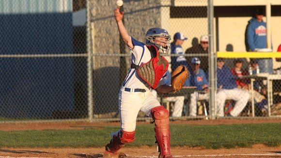 Madison catcher Jordan Baker makes a throw Monday night in Marshall.