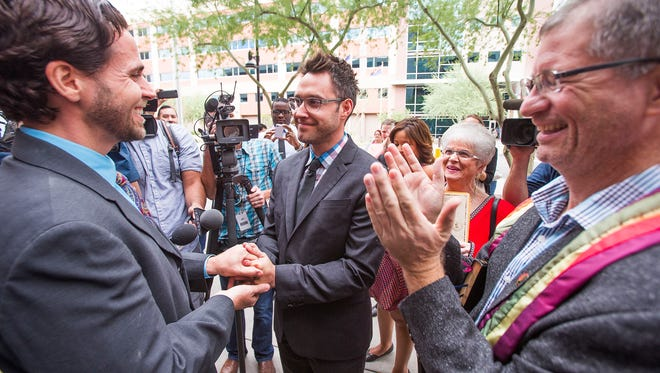 David Larance, 36 (left), and Kevin Patterson, 31, both  of Phoenix, get married outside the Clerk of The Superior Court office in Phoenix. They were the first couple to get married in Phoenix minutes after receiving their marriage licenses after gay marriage was legalized in Arizona Friday, October 17, 2014.   The Rev. Dr. John Dorhauer of the United Church of Christ (right) presided.
