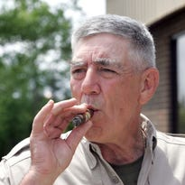 "FILE - Retired Marine Gunnery Sgt. R. Lee Ermey takes a break for a smoke outside New River Air Station's Staff NCO club, in this May 15, 2006 file photo taken in Jacksonville, N.C. Ermey is living the Marine Corps' mantra: ""A Few Good Men."" The former Marine drill instructor and host of The History Channel's ""Mail Call"" was in Missoula on Monday to film a segment for his upcoming series ""Locked and Loaded"" when he said he found some cash. A lot of cash.  Ermey told the Missoulian newspaper he thought: ""Some poor guy right now is probably getting fired, probably having the worst day of his life. So what we did was we went right down to the Wells Fargo bank and deposited it for him."" (AP Photo/The Daily News, Randy Davey, File)"