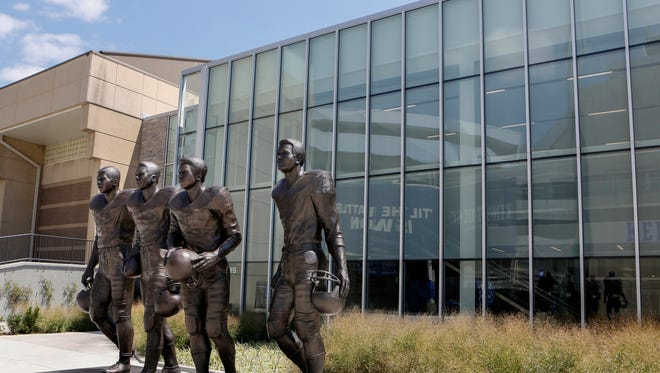 The statue outside Kentucky football's practice facility contains, from left to right, Greg Page, Nate Northington, Wilbur Hackett and Houston Hogg.
