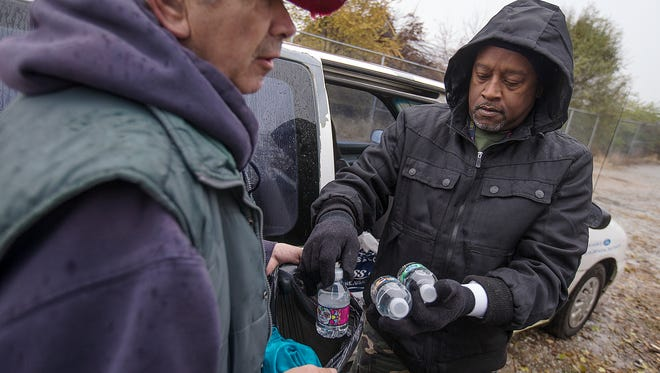 John Wheeler (left) receives water and food from Rodney Jackson near the entrance to his homeless campsite along the White River, Indianapolis, Tuesday, Dec. 6, 2016. Wheeler is a homeless Marine veteran who receives resources from Hoosier Veterans Assistance Association, where Jackson is an outreach worker. Wheeler has ultimately chosen to live on the streets, not wishing to carry the burden of monthly bills and material possessions.