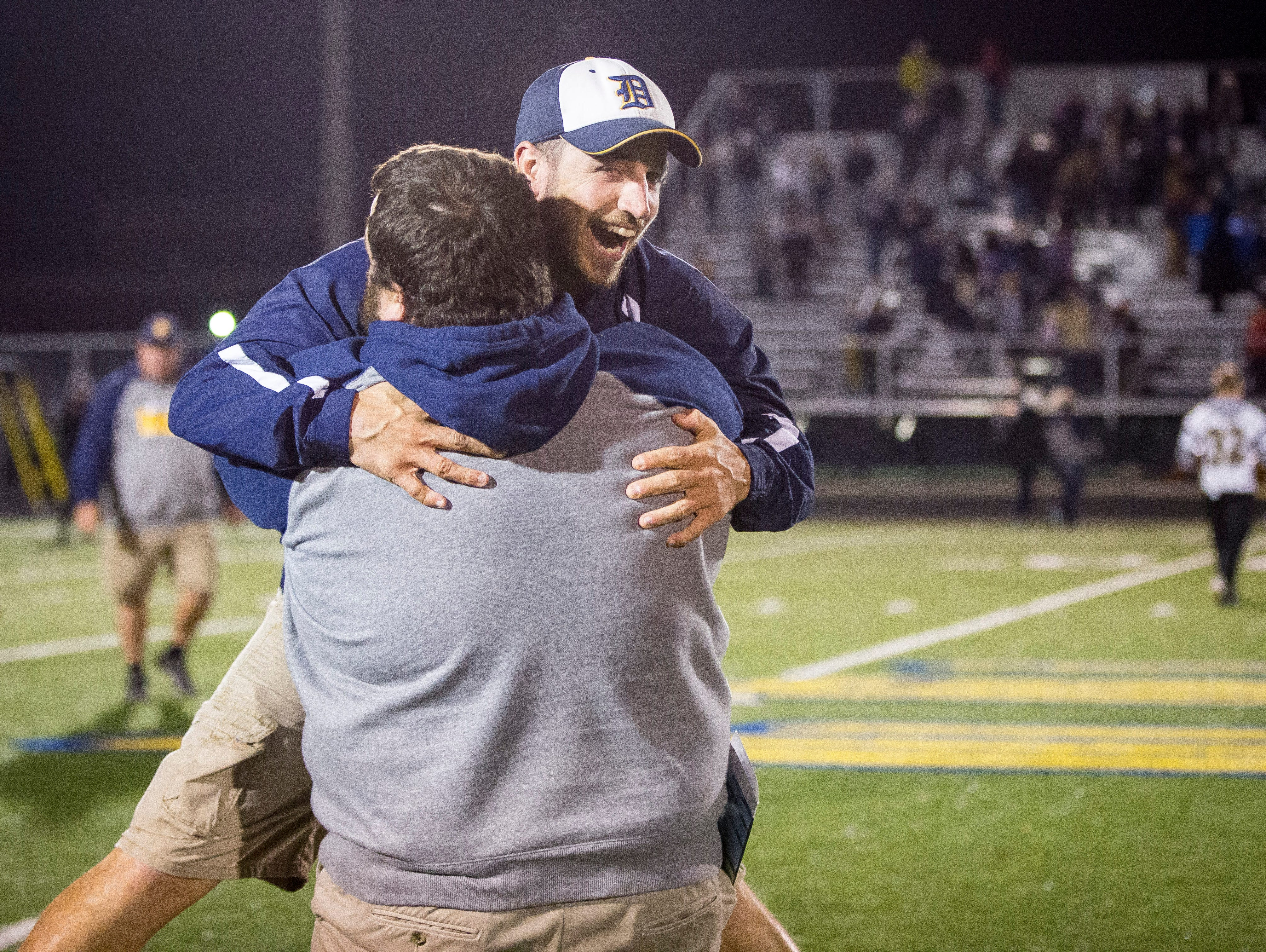 Two of Delta's assistant coaches embrace after a close victory against Mt. Vernon Friday night at Delta High School. Delta won the game 12-6.