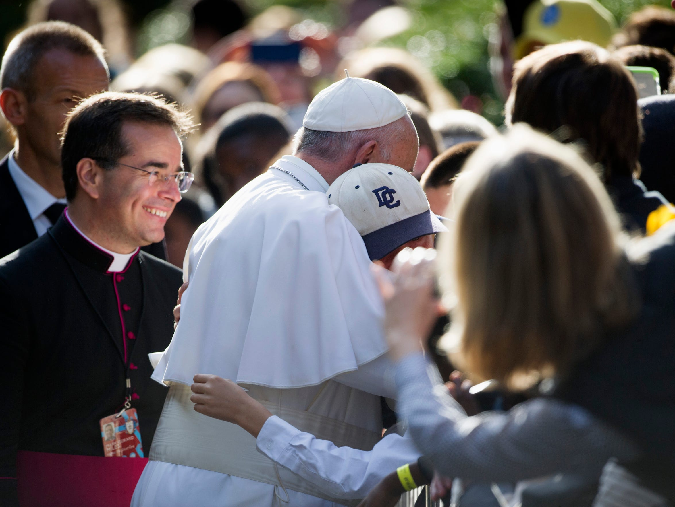 Pope Francis hugs a young boy while greeting school