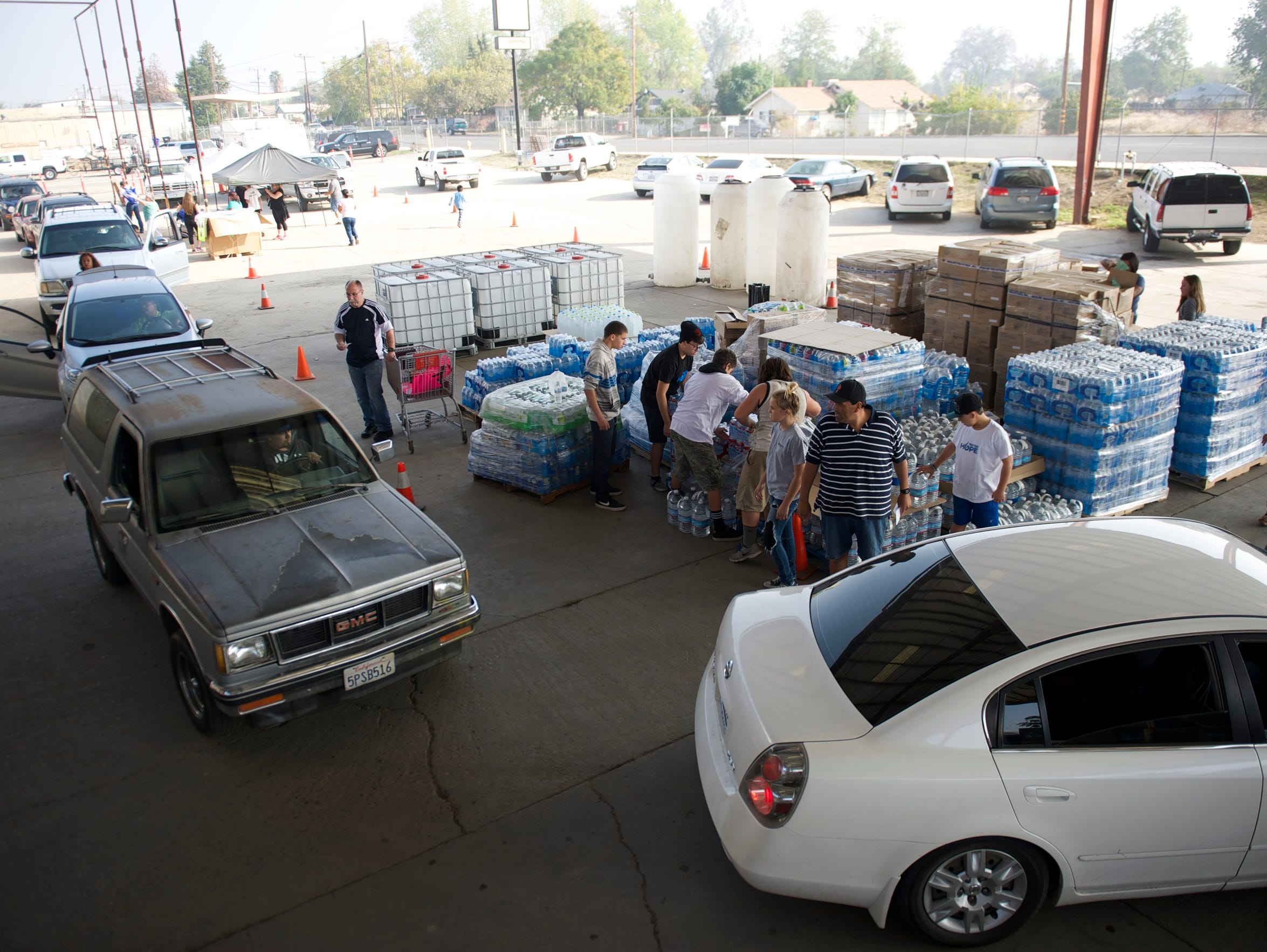 People line up in their cars to receive donated cases